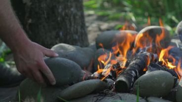 Go with your pallette, taste of elouan - campfire image, hand placing a rock in a fire ring