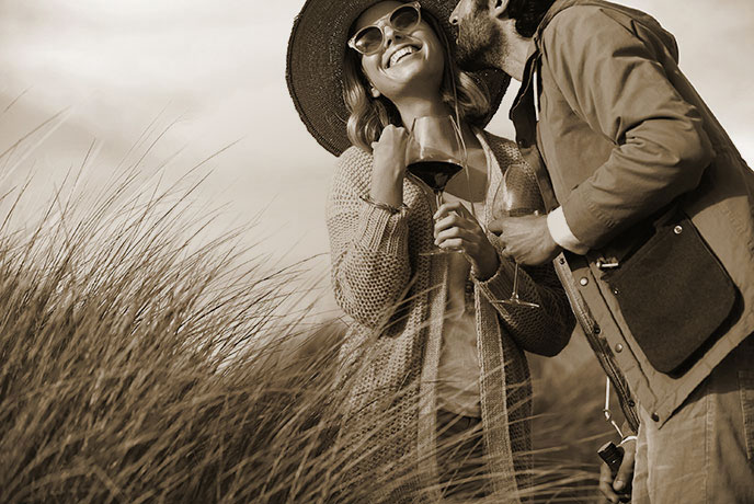 Belle Glos lifestyle sepia photo - a couple embracing while sharing a glass of wine on a wind-swept beach
