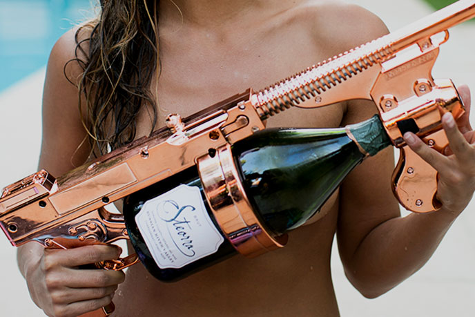 Steorra lifestyle image, lady holding rosé colored champagne gun with bottle of Steorra champagne