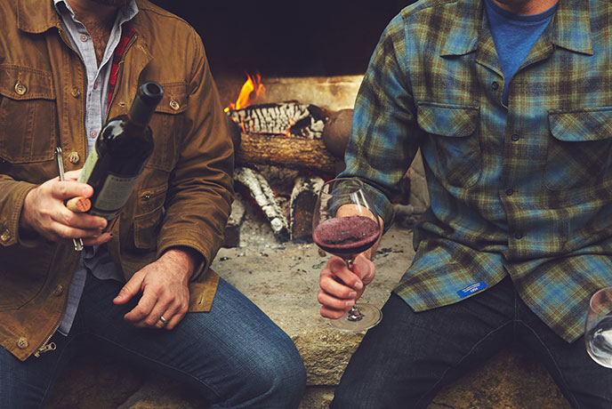 Rustic Carne lifestyle photo featuring Joe and friend sharing a bottle of wine in front of a fireplace