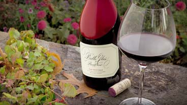 Belle Glos Last Alturas bottle with wine glass set atop a vineyard table