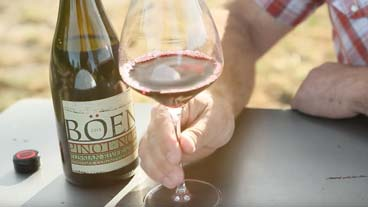 Boen bottle shot with hand holding glass of wine on a sunny day
